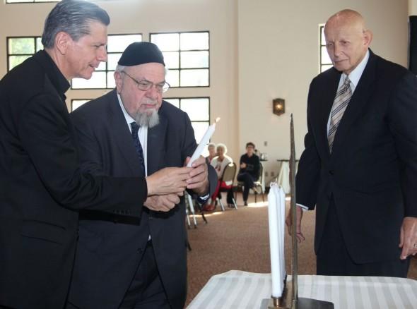 Archbishop Gustavo Garcia-Siller (left) and Rabbi Aryeh Scheinberg light candles on the Menorah, as Rabbi Sam Stahl observes, at the interfaith celebration.